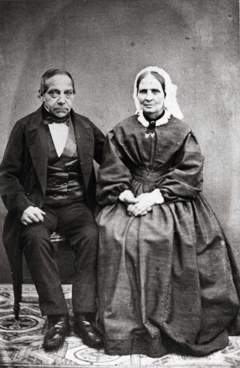 Dobbeltportrett, Justine Andresen med mann. Kvinne i kjole og hodeplagg og mann sittende i fotoatelier. Han var kjøpmann i Østfoldby.