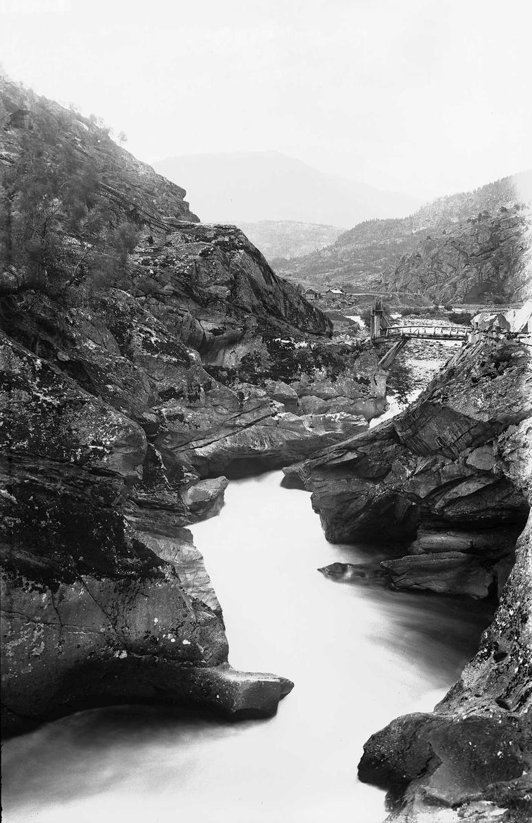 Fjellandskap med elv og trebro fra ukjent sted i Norge. Det likner litt på Tuftebrui, gamle bru for Normannsslepa ovenfor Geilo, tatt nedenfra mot Ustaoset?