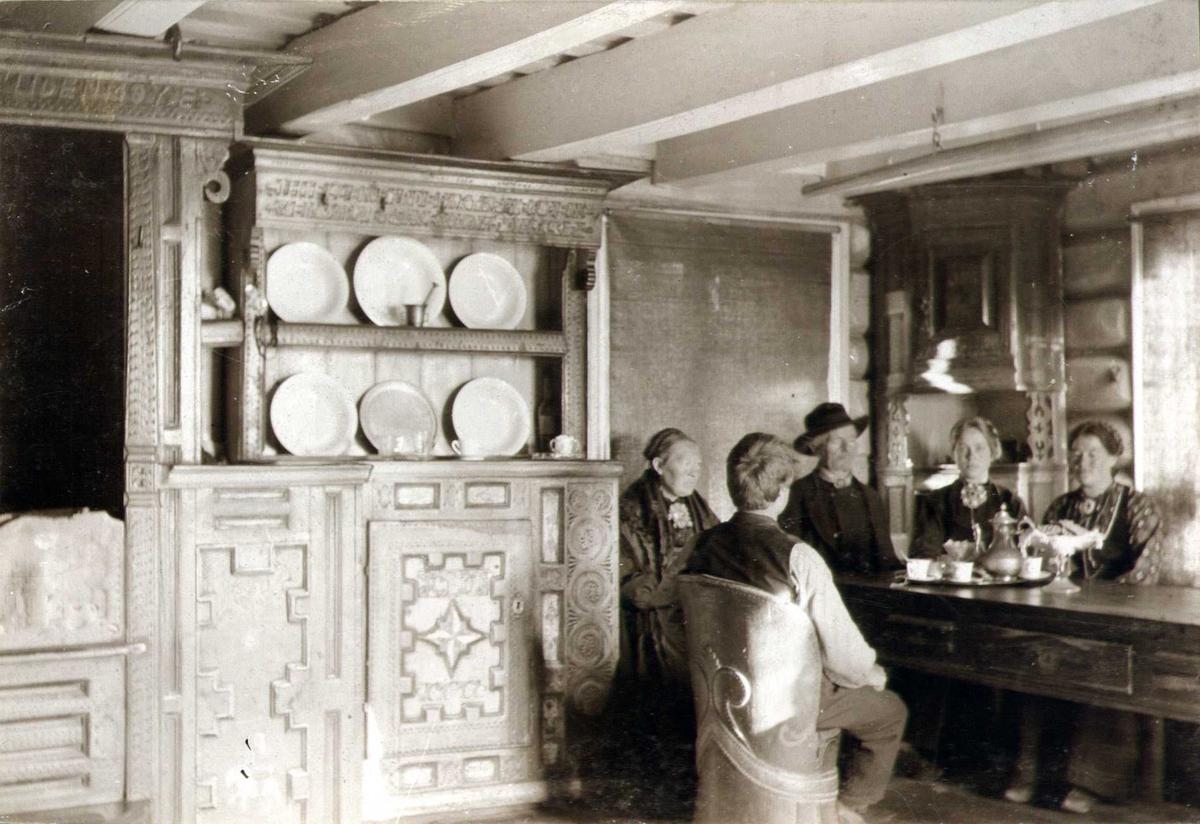 Stueinteriør innredet av Tarald Olsen i 1811, Skoje, Sauland, Hjartdal, Telemark. Familie sittende rundt bordet. Fotografert 1907.