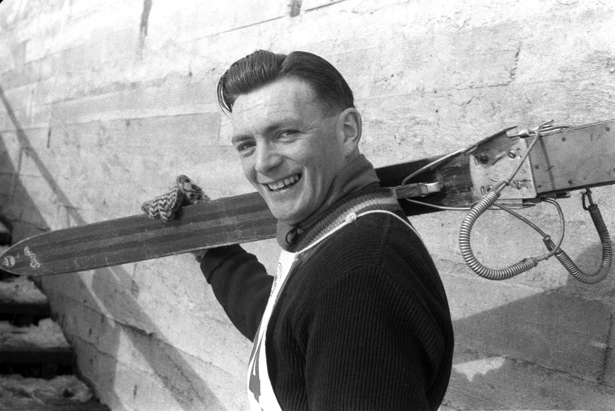 Hopper på vei opp i hoppet med skiene på skulderen. Holmenkollhopp 1953. Fotograf Dagbladet
