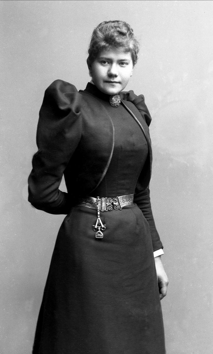 Portrett, kvinne i svart kjole med belte. Brosje i halsen. Frøken Schriver.