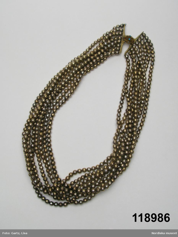 """Huvudliggaren: """"Halsband av silver, 8 rader silverpärlor, med litet, ovalt, förgyllt lås i filigranarbete, med kronformigt överstycke och infattade blå och röda stenar, vid sidorna fäste för pärlbanden. Ej svenskt. (Enligt uppgift brydsmycke från Småland)."""""""