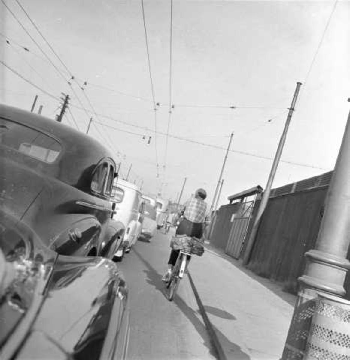 Bybilde, ant. Oslo, 1956. Gateløp med biler og syklist.