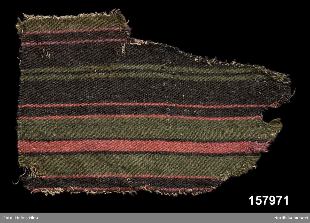 Tygprov. Varp: 1-trådigt S-spunnet oblekt lingarn, 40 trådar/10 cm. Inslag: 1-trådigt S-spunnet ullgarn, cirka 120 inslag/10 cm. Inslagsrips som täcker varpen helt. Tvärrandigt. Mönsterrapportens längd är 18,5 cm. /Berit Eldvik 2002