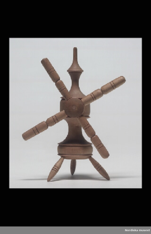 Inventering Sesam 1996-1999: H 13  B 11,5  cm Leksaksvinda, nystvind, av obehandlad svarvad björk, kontursvarvad ståndare på tre utsvängda ben, vinda med fyra armar. Troligen från 1800-talets slut. Birgitta Martinius 1997