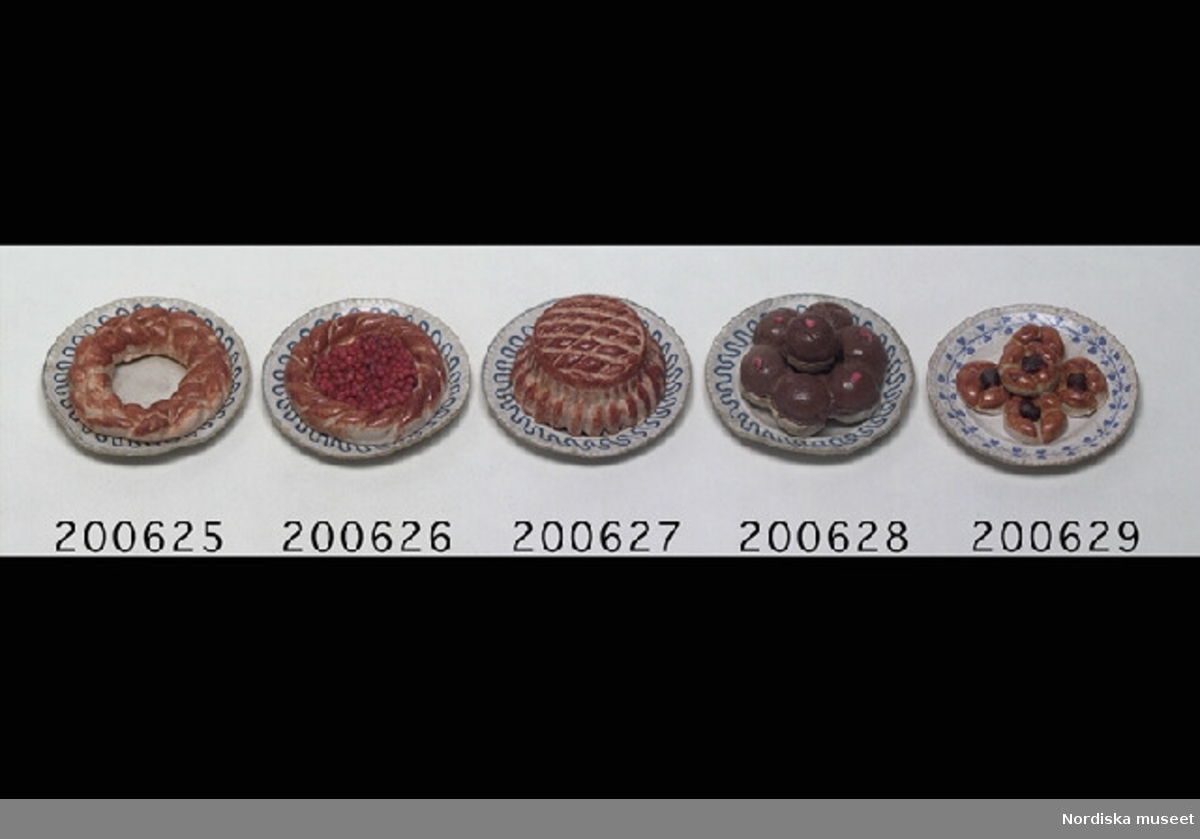 Inventering Sesam 1996-1999: Diameter 4 cm Kakfat med vetekrans av konstmassa på papptallrik med blå dekor. Tillhör dockskåp inv. 200.513. Birgitta Martinius 1996