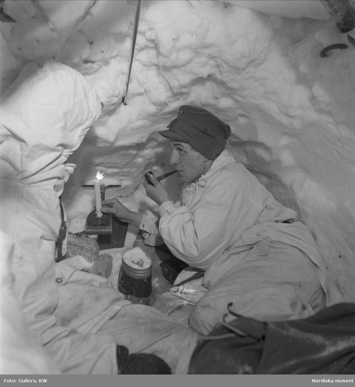 Soldat i snövärn röker pipa vid ett tänt stearinljus