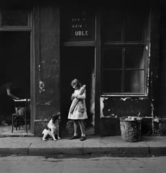 Flicka och hund på trottoar i Paris. Flickan håller i ett lå