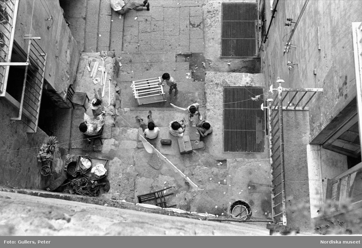 Fågelperspektiv. Bilden tagen rakt uppifrån ner på gata eller gård. Barn som leker. Kvinna som sitter på stol. Italien