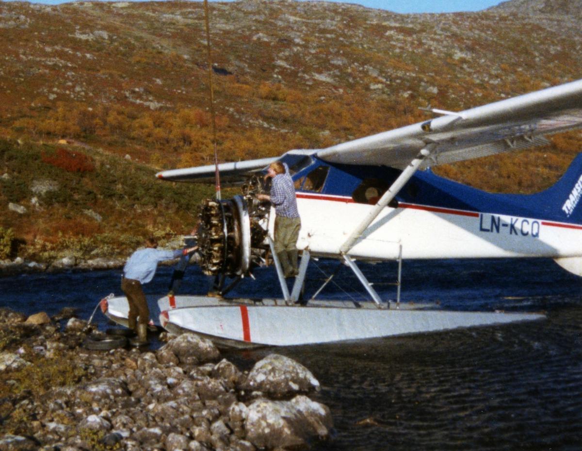 Ett fly i vannkanten, LN-KCQ, DHC-2 Beaver. Flymotoren henger i ei stropp fra Helikopter. To personer ved flyet