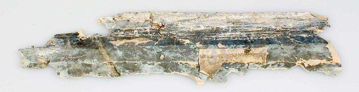 Ett mindre tapetfragment av papper, målade ränder i grått, blågrått och ljusare blå färg. På baksidan märkt: VII S.