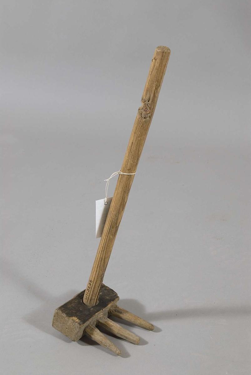 Potatiskrats, helt av trä, i form av liten kratta med tre itappade grova snidade pinnar. En pinne lös.