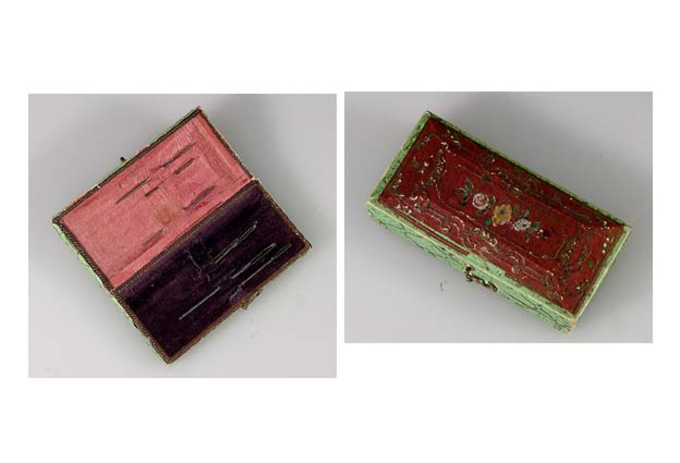 Nåletui, ask av trä klädd med rött mönstrat och grönt mönstrat papper. Inuti klädd med rosa siden och lila sammet. Innehåller sju stoppnålar.