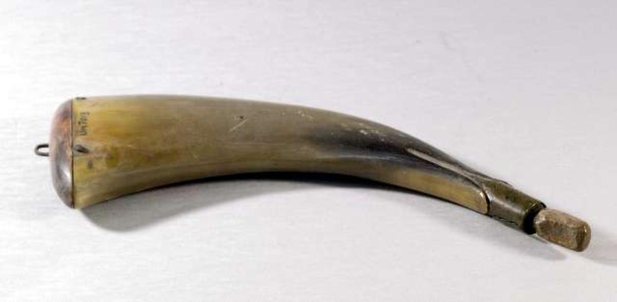 Kruthorn av gulgrönt horn. Botten och propp av trä. Mynningen skodd med mässing. Inristat: JAF. Mässingsögla.