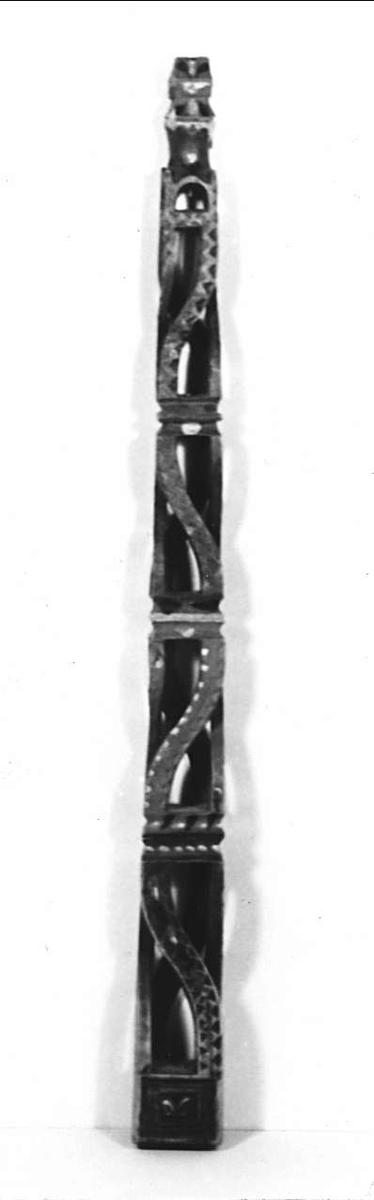 Linfäste (linspira) av trä. Rektangulär, uppåt avsmalnande form. Fyra genombrutna avdelningar med S-formigt böjda hörnstavar med veckband och kilsnittsband. Målning i blågrönt, gult och rött. I speglar nedtill tulpan i  rött, vitt och svart.