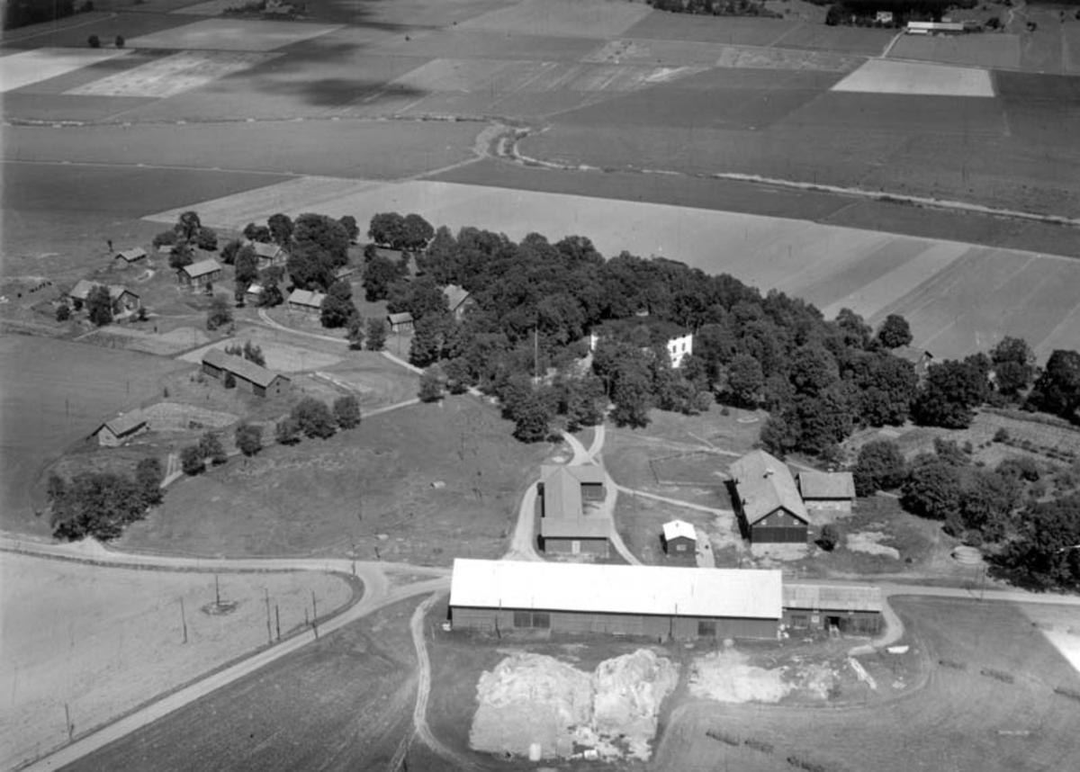 Flygfoto över Landsberga gård, Biskopskulla socken, Uppland med omgivande bebyggelse och marker 1952