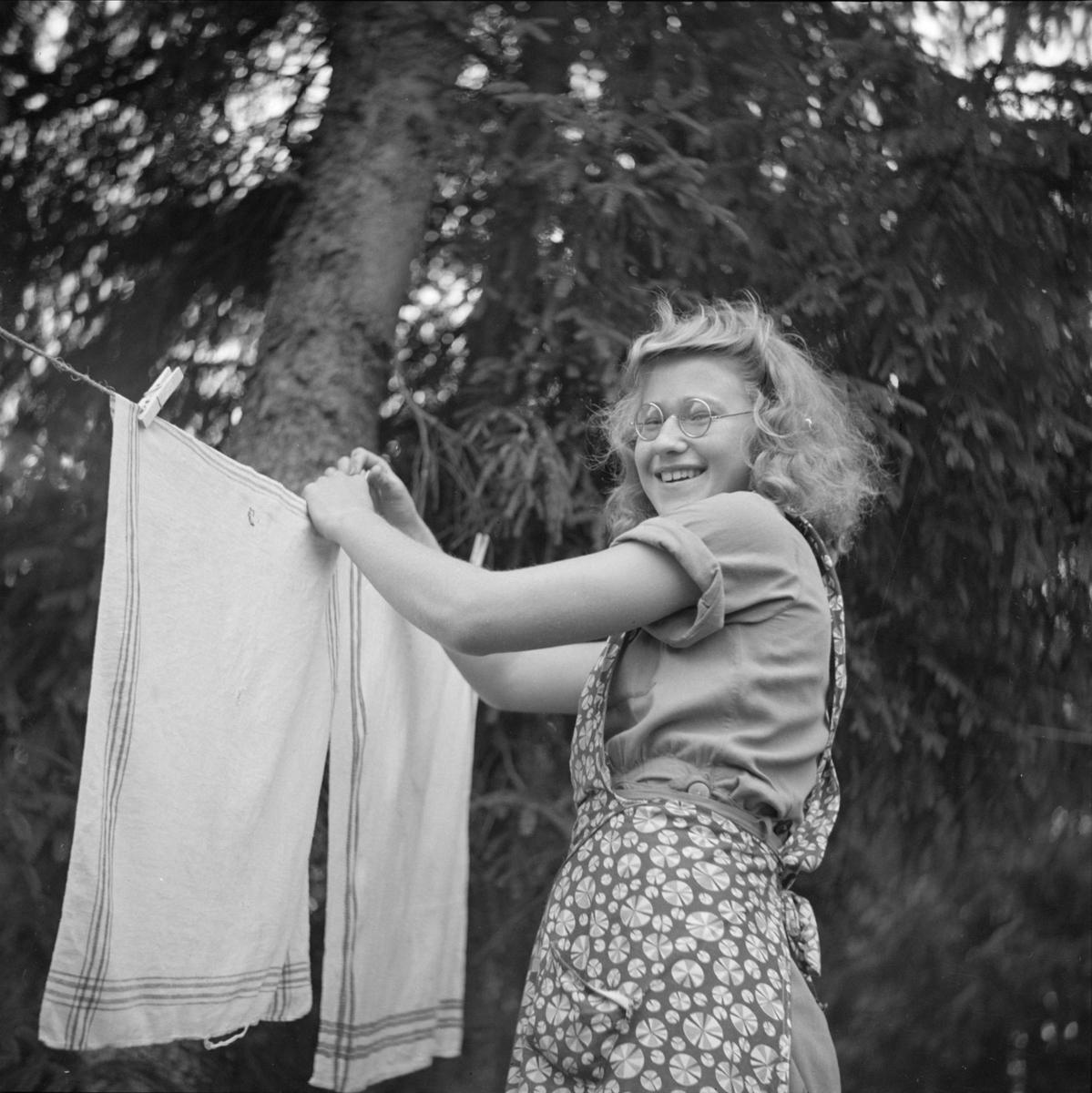 Kvinna hänger upp tvätt på beredskapsläger i Skuttunge, Skuttunge socken, Uppland 1940