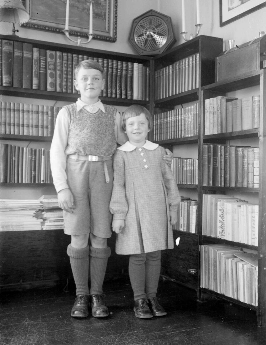 Gutt og pike i stue. Gunnar og Vesla foran bokhylla.