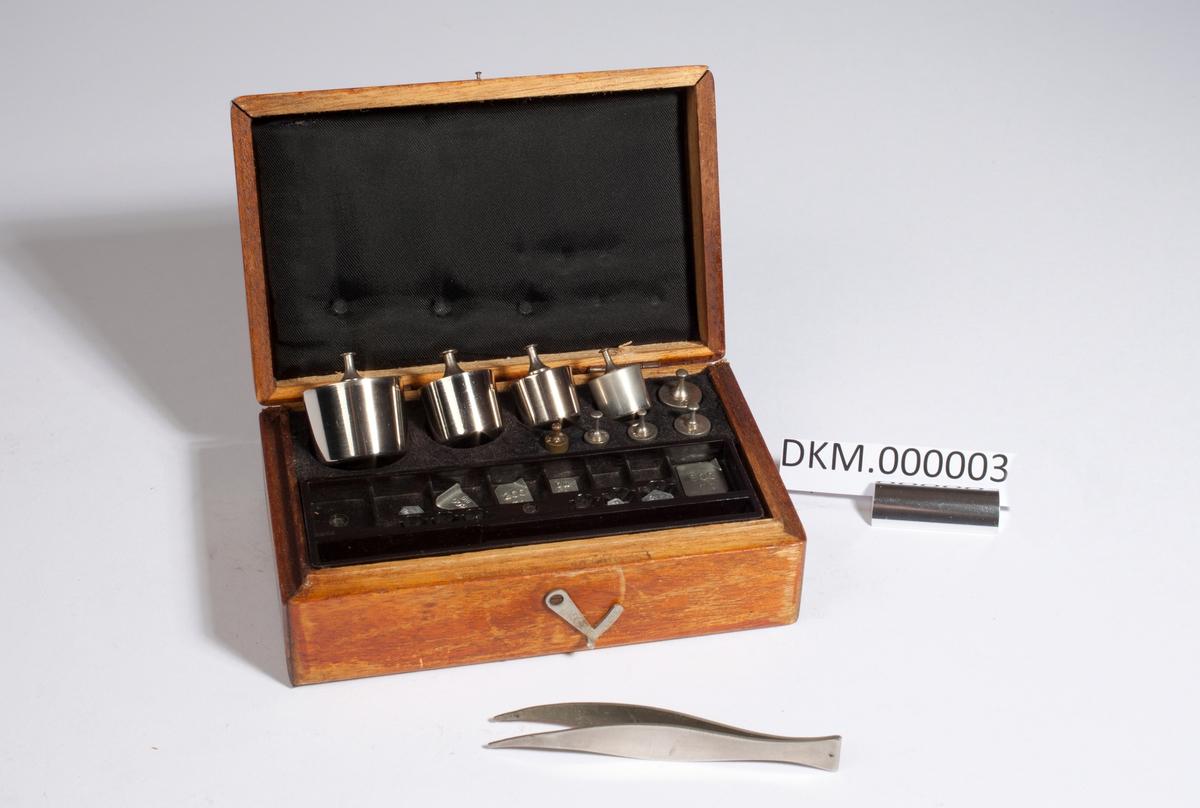 Kasse med åtte sylinderlodd og ti platelodd.