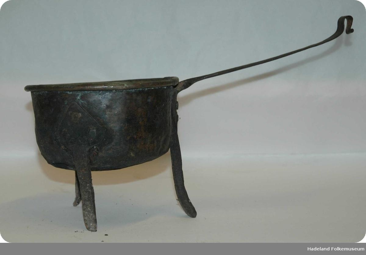 Rund kobberpotte. 3 bein av jern er naglet fast til kjelen. Det ene beinet og håndtaket er laget av et stykke. Håndtaket er bøyd til en krok i den ene enden.  Potta er noe skjev fordi det ene beinet er kortere enn de andre.