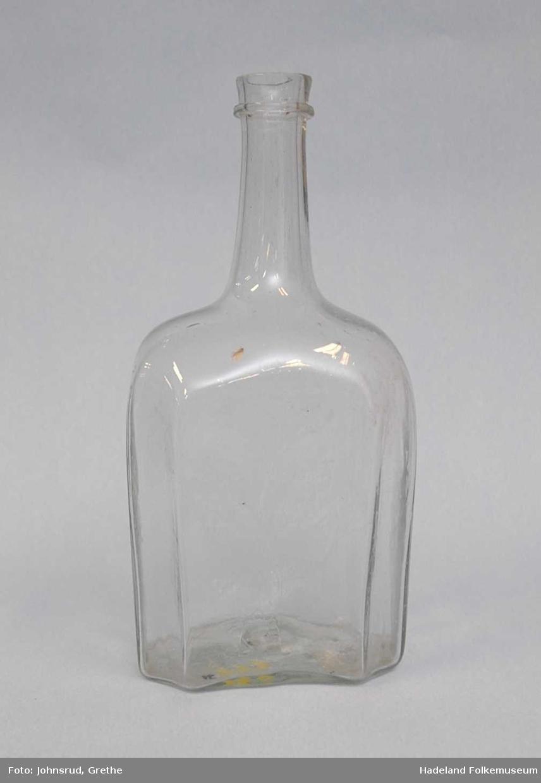 Åttekantet flaske i klart glass. Rørformet hals med ring mot toppen.  Dekorert med slipte blomster.