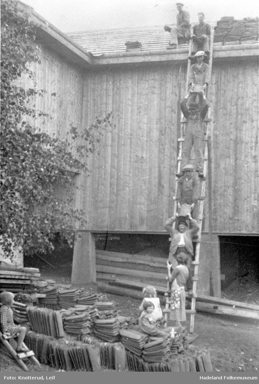 Låve bygges i Knotterud og takstein legges på taket. Folk i stige sender opp takstein til låvetaket.