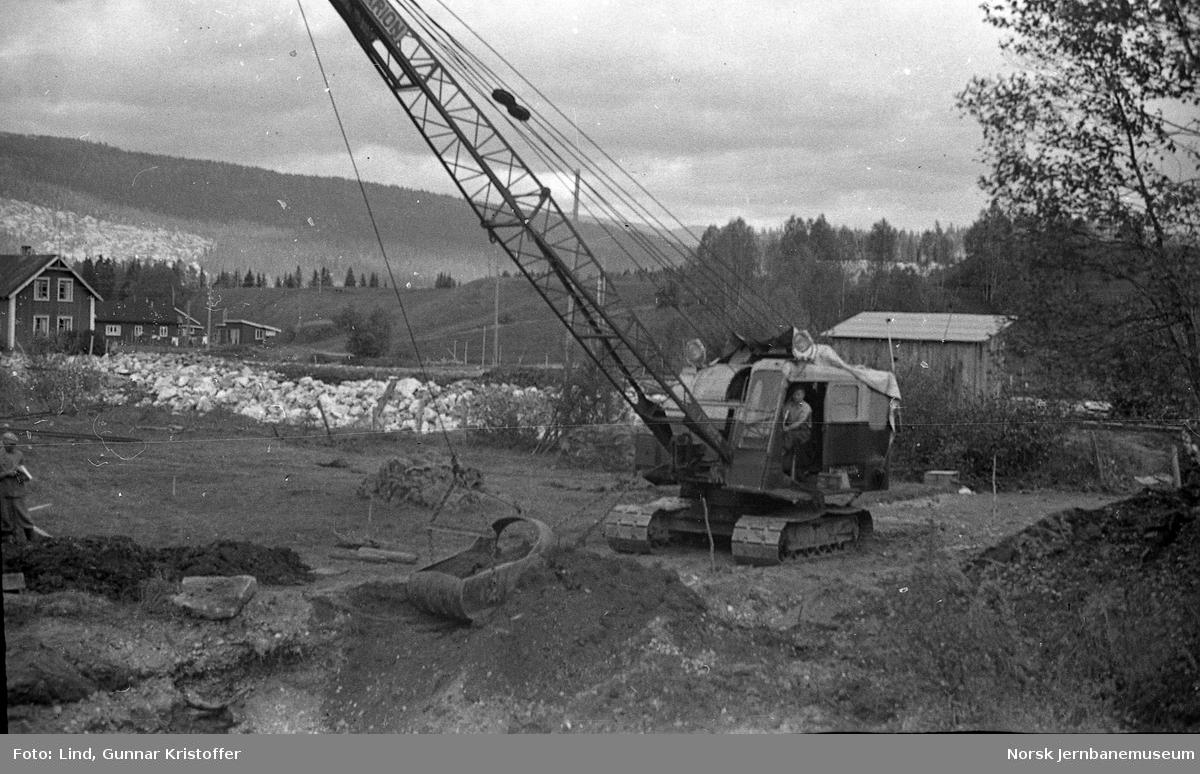 Dunderlandsbanens ombygging : Marion gravemaskin i arbeid med bekkeregulering av Leirbekken
