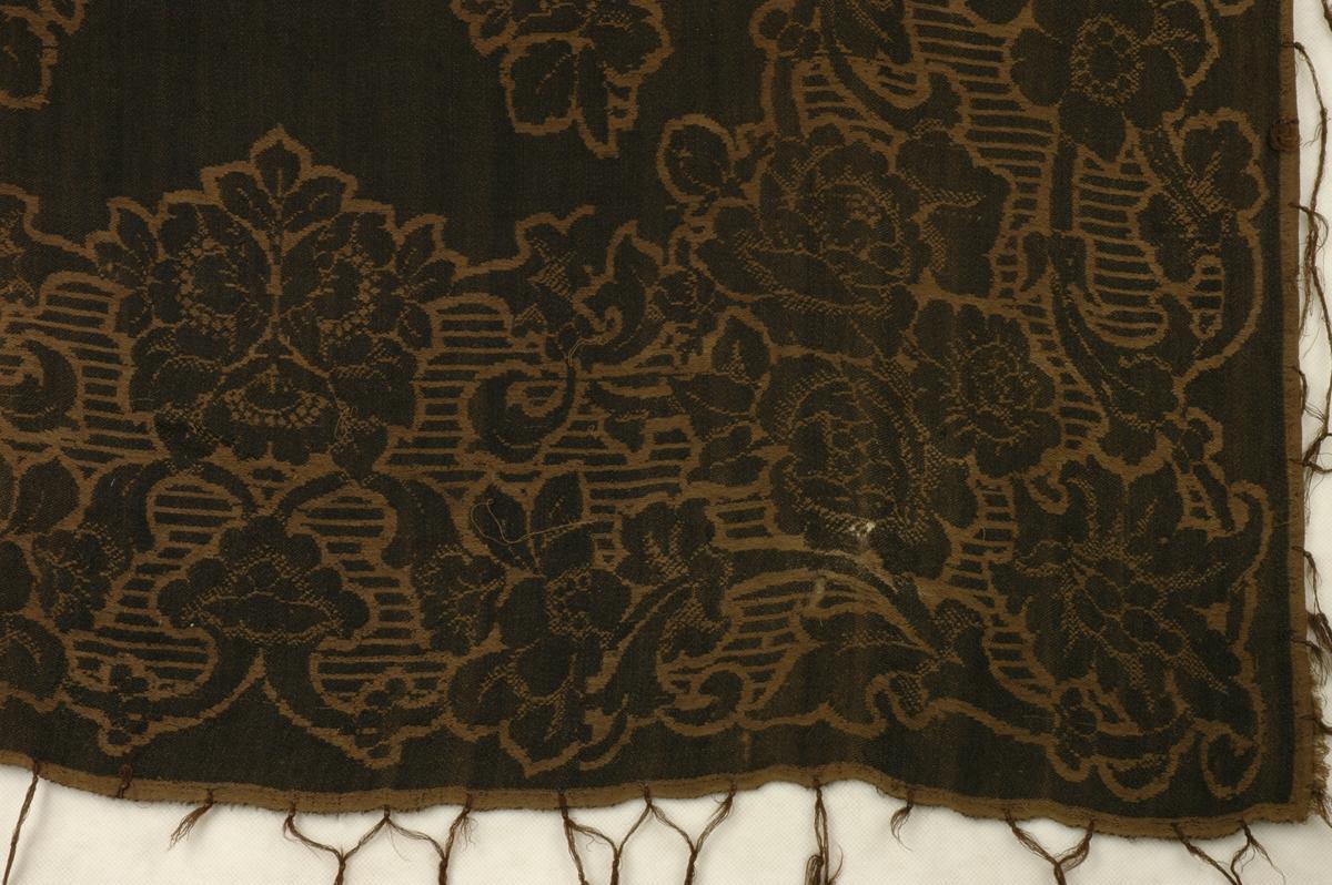 Stort, damaskvevd ullsjal med påknytta frynser. Innvevd blomstermønster.
