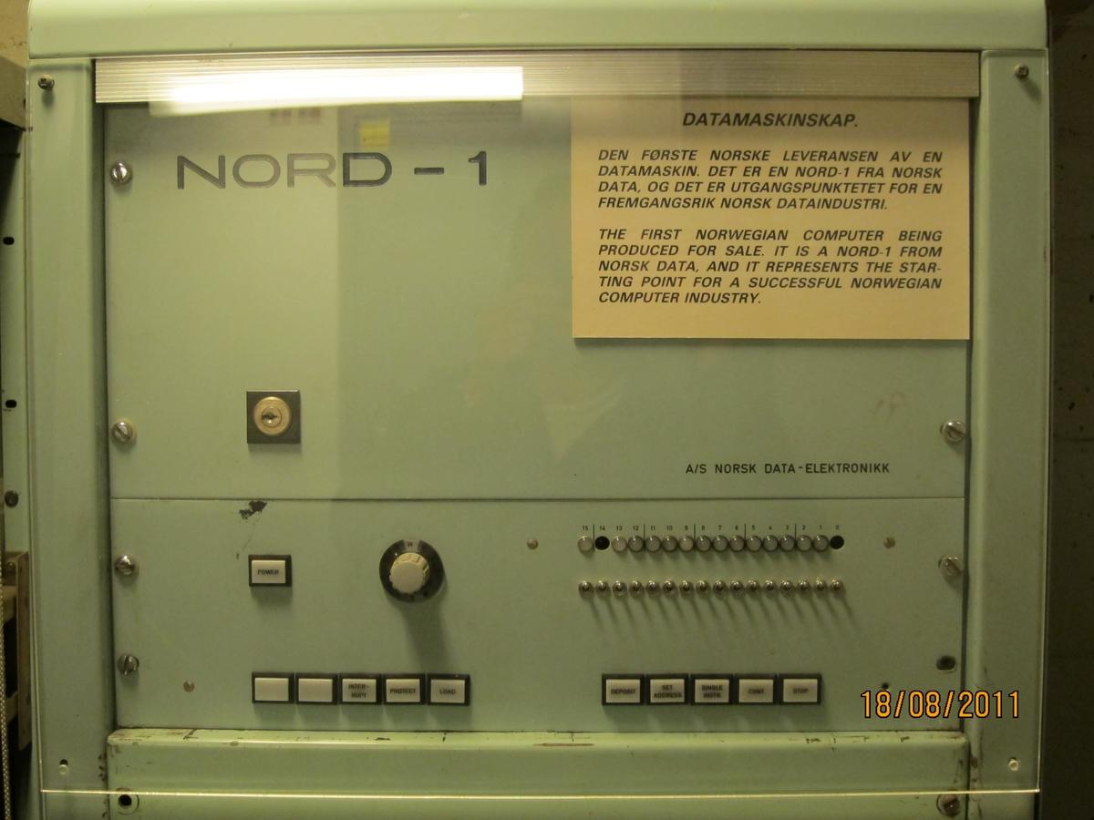 Pult med radarskjerm, brytere og display for 'miles',  'degrees north' og 'minutes'. Pult mrk. A, 3 skap mrk. B, C og D. Pulten og 5 skap sto ombord i 'Taimyr', Wilhelm Wilhelmsen´s rederi. (NSM 13028) Prosjektet startet i 1967, finansiert ved hjelp av midler fra  Norges Teknisk-naturvidenskapelige Forskningsråd. 26. januar 1968 ble kontrakt undertegnet med Norsk Data , og anlegget ble satt i drift i 1969. Det har hatt stor betydning for utviklingen, og var verdens første. Dette er forløperen til Norcontrol´s databridge, som i 1981 var installert på 210 skip.