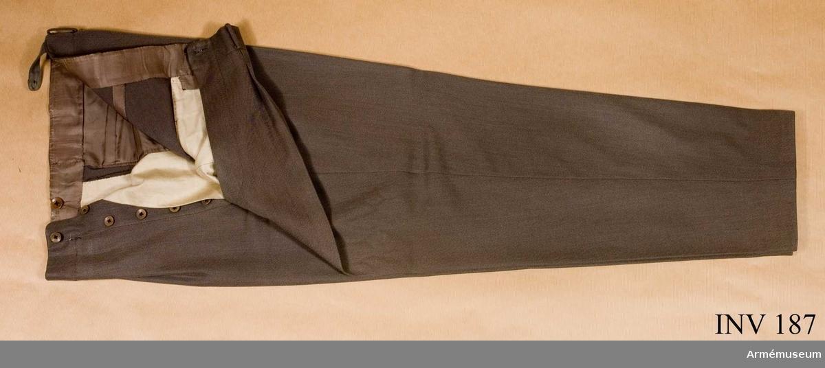 """Byxan är grå-brun-grön med 3 st fickor, 2 snedskurna och 1  rakskuren. Gylfen knäpps med 6 st bakelitknappar. På insidan i  midjan 4 st knappar (två i metall märkta """"For Gentlemen"""" och en märkt på baksidan """"Eduard Schriever"""" och på framsidan E. Söderlunds Militärskrädderi). Två hängselstroppar med  vardera 1 st bakelitknapp. Byxan är märkt Erik Söderlunds  Militärskrädderi Stockholm. Kapten H. Decke 1943 9 23."""