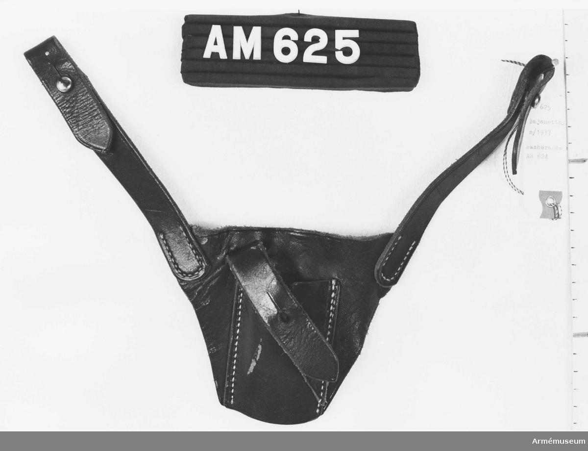 Samhörande nr är 624-625. Bajonetthylsa t livrem med axelrem m/1937. Mått: plattans höjd 220 mm. Av mörkbrunt läder med vita metalldelar, tillhör livrem m/1937. Hylsan består av en triangelformad platta och från dess bas utgår två remmar, 150 mm långa, vilka skall fästas vid de ringar som finns på livremmen (AM 624). På plattan är stickad en rektangulär hylsa i vilken  bajonetten skall placeras.