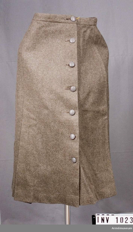 Samhörande nr är 1017-1059, 1062-1063, 1072-1073.Kjol m/1942, ylle.Storlek 42. Av gråbrungrönt ylletyg. Omlottlagd med knäppning i vänster sida med sju knappar i färg med kjolen. Mellan 2:a och 4:e knapphålet finns en  fickpåse på avigsidan. Då kjolen knäpps vid sin 3:e knapp uppifrån stänger man även fickan. Linning i midjan. Vänstra kjoldelens underliggande våd knäpps fast vid linningen mot avigsidan för att ej hänga ned. Det finns ett till hälften nedsytt motveck på höger sidas framvåd. Vändsydda sidsömmar. Ett till hälften nedsytt motveck mitt bak. Fållen nedtill uppstickad på maskin. Knapparna är kupade och refflade. Kjolen märkt på linningens insida: Cegece  42 L, tre kronor- stämpel 42 1944.