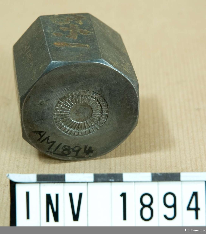 Åttakantig stans med kokard, d 21 mm, i mitten. Skall efterhärma två lager plisserat siden med pistill i mitten.  Samhörande nr är 1677-1699, 1800-1899, 2100-2123.