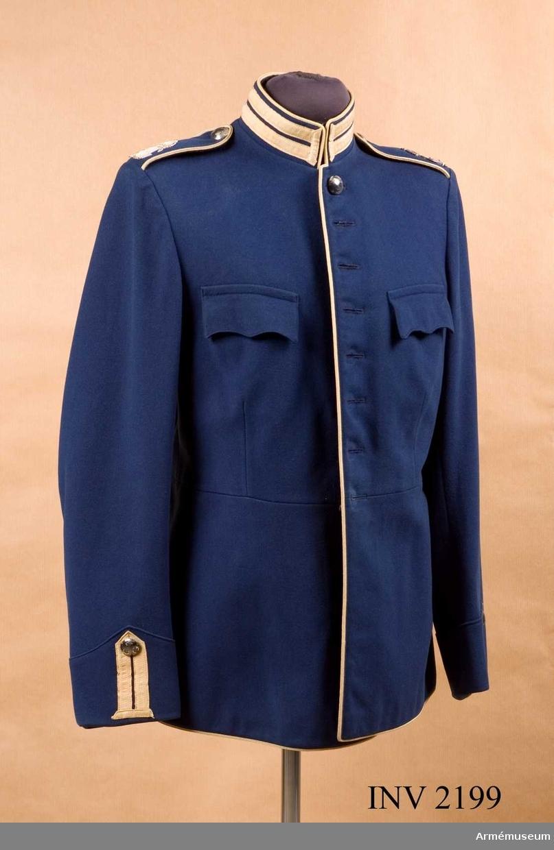 """Mellanblått kläde med vita knapphål och passpoaler av redgarn. I axelsömmen fast axelklaff med passpoal och K 1:s knapp m/1845 större, G VI A:s namnchiffer m/1950-1960 i silver. (Vitbehandlat). Knäppt med åtta reg.knappar. Två bröstfickor med fasonerade ficklock. Två innerfickor, den ena vid vänster bröst med märkning  tre kronor """"98L"""". Den andra fickan höger skörts insida används att lägga."""
