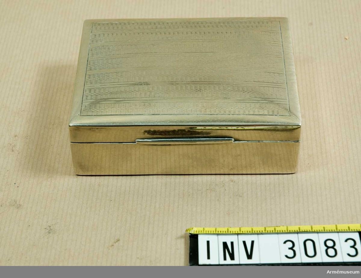 """Uppfällbart lock. På lockets utsida ett randat mönster. Invändigt klätt med """"cedrela odora'ta"""", västindisk ceder eller kubaceder, ett välluktande virke som använts just i cigarrlådor."""