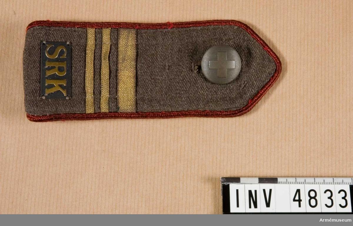 Gott skick. Längd: 250 mm, bredd: 55 mm. Av  grbrgr diagonal, troligen cellull, ett kristidmaterial under  kriget. Axelklaffen är kantad med röd fyrkantsgalon i silke och försedd med en grå bricka med bokstäverna SRK = Svenska  Röda Korset. Gradbeteckning för Överstelöjtnant samt knäppes  med röda korsets knapp 1939 av större modellen. Användes på  kappa och trenchcoat m m.Bataljonsläkare Gerhard Rundberg har deltagit i Bernadotteexpeditionen och Korea ambulansen.