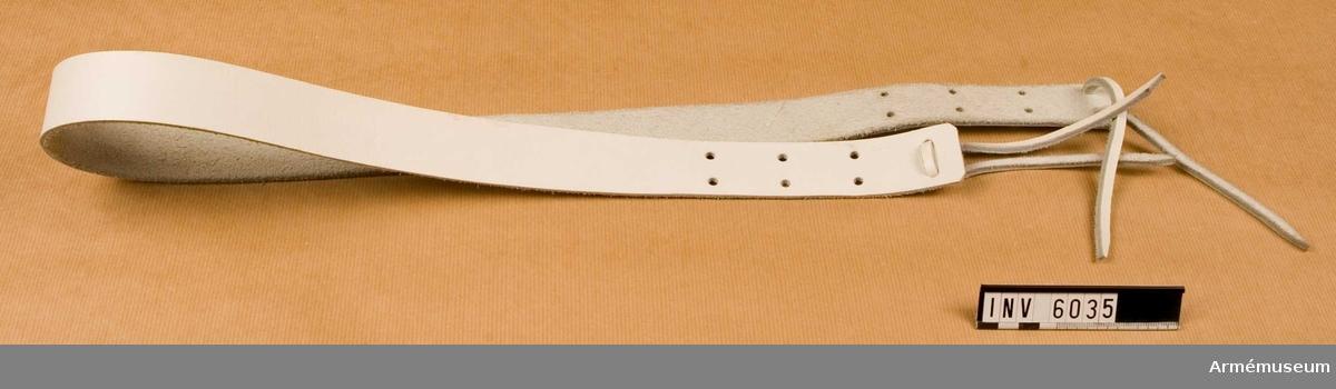 """Samhörande nr är 5828-5899, 6000-6099, 6200-6212.Bärrem t trumma m/1954, musikavdelning.Av vitt läder m hål i ändarna och läderrem f fastsättning vid trumman. Två identiska remmar tjänar som bäranordning f trumman då den fraktas; bäres som en ryggsäck. Källa: Bo Ancker """"Vaktparaden kommer"""". Uni A 6:502."""