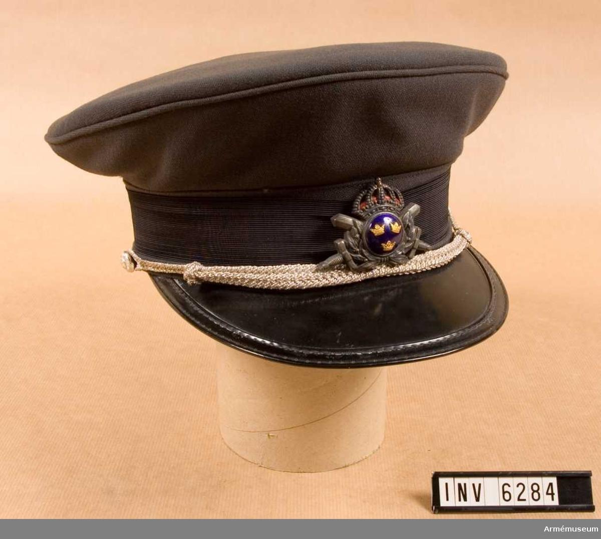 Storlek: 57. Stålgrått ylletyg m svart skärm (grön undersida), stålgrått mössband, mössmärke i silver m/1960 och mössträns i  flätad silvertråd. Det är trängens uniform. Se bilaga 19810522 nr 345.