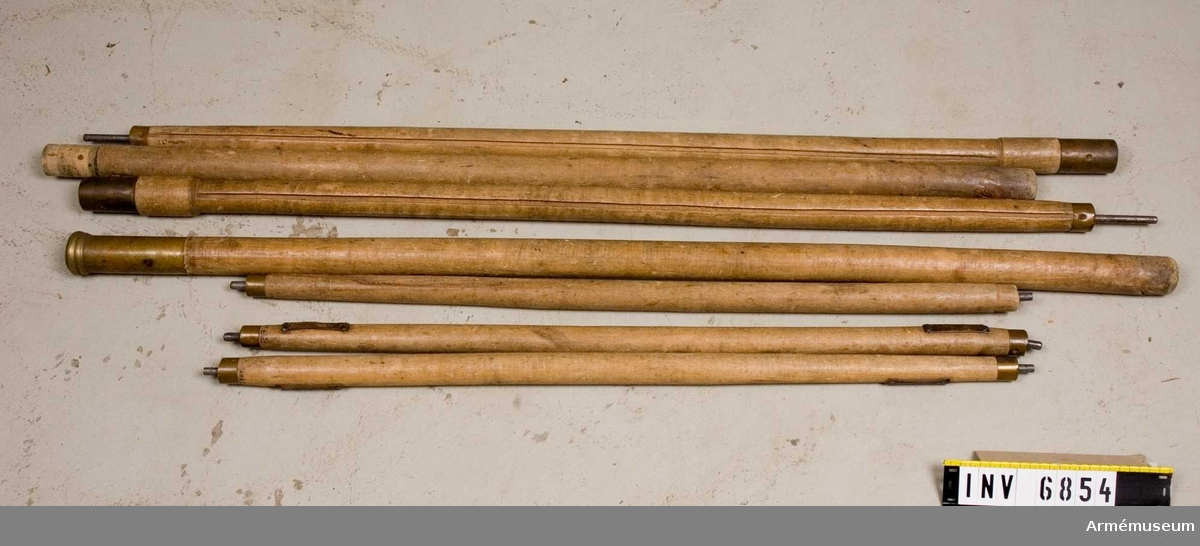 Takstänger 850 mm, 3 st. Mittstänger 1150 mm och 1250 mm, antalet 2 st vardera. Takstänger mässingsbeslagna i båda  ändarna samt 20 mm tenar, avsedda att fästas i  mittkransen och  de fyra hörnhålen.  Därmed hålls taket utsträckt. Varje stång  har ett 80 mm långt läderband i var ände. Vid förvaring träs  ett sadelgjordsband genom läderbandet och håller därmed  stängerna samman vid förvaring.  Mittstänger längd 1150 mm och 1250 mm bildar en mittstång. Den 1150 mm långa stången är grövre och har en krans som löper runt stången. Kransen har  fyra hål i vilka takstängerna skall stickas in i vid montering.   Stängernas andra ände skall stickas ut genom tältets fyra hörnhål. Kransen är höj och sänkbar. Mässingsbeslagen. Genom  att stoppa en spik genom det hål som finns nedanför kransen kan  man hålla denna på plats.   Samhörande nr är AM.6852-8