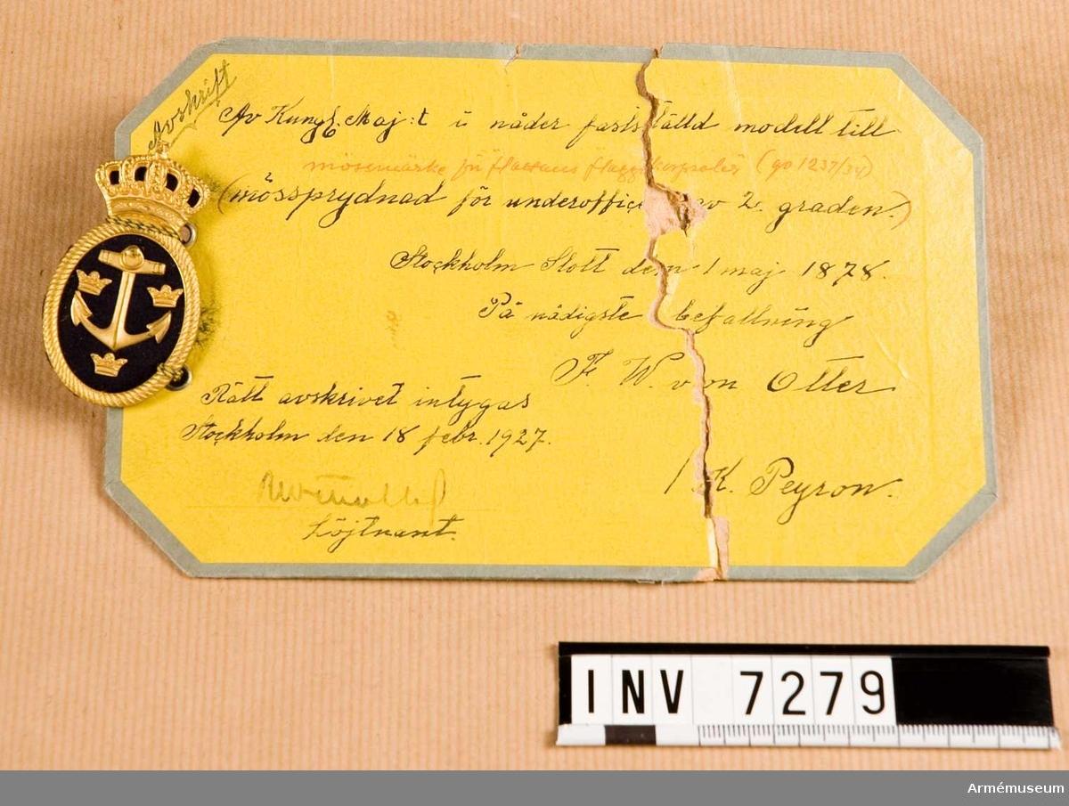 """Ett ovalt märke med ankare, tre kronor inom en krans krönt med krona, och med botten av mörkblått kläde. På frånsidan märkt: MEA. Klädets färg M. Metallens färg D. Nyskick 111. Sammanhänger med modellapp med text: Avskrift / Av Kungl Maj:t i nåder fastställd modell till mössmärke för """"flottans flaggkorpraler"""" (go 1237/34) mössprydnad för underofficer 2. graden. Stockholms slott den 1 maj 1878. På nådigste befallning  F. W von Otter / K. Peyron."""