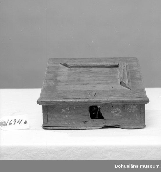 Rektangulär med pulpetlock. Locket har en spegelist, varav två bitar saknas. Fram- och kortsidorna har spår av rosmålning. Nyckelskylt och nyckel saknas. Inuti finns en läddika med en äldre etikett i från ca sekelskiftet. Locket saknar två av kantlisterna.  Litt.; Knutsson, Johan, Friargåvor, Nordiska museets förlag, Stockholm, 1995, s. 56.  Ur handskrivna katalogen 1957-1958: Omålat träskrin, m.sluttande lock. a) L.30 Br. 22,5 H. 16,5 cm;  Ett mindre fack m. lock inuti; gångjärnen och låset trasiga; sydelen saknas. Locket b) Mått: 31 x 27 cm; 2 kantlister och 2 profillister saknas.  Lappkatalog: 84
