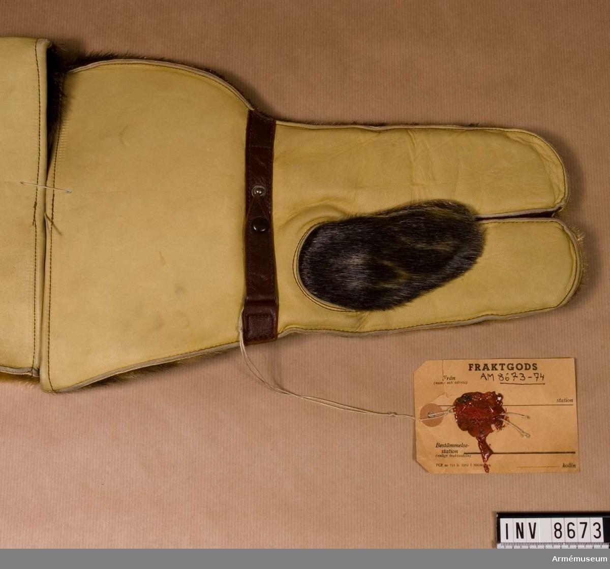 Handske arbm/1952, motor-. Motorhandske, arbetsmodell 1952. Längd 360 mm. Vikt 261 g. Lammskinnsfodrad med utsidan av sälskinn och handsidan av kromläder. KAFI beslut 5.2.1952, dnr 4892/51 UtrB.KAFI = Kungl Arméförvaltningen intendenturavdelningen.
