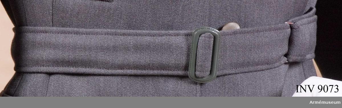 Skärp till jacka m/1942kv, SKBR. Av samma tyg och färg som jackan. Är försett med ett målat spänne i metall som knäpps med hake mot en metallhank på motstående sida. Spännet går att skjuta till önskad vidd på skärpet.