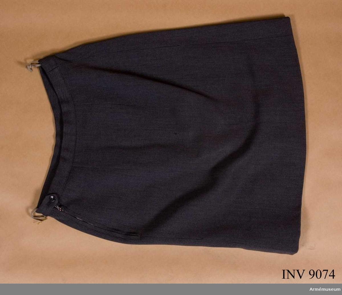 Av samma tyg och färg som jackan. Kjolen är ofodrad, försedd med linning i midjan, två passpoalerade fickor framtill och ett motveck mitt fram. Blixtlås i vänster sida.