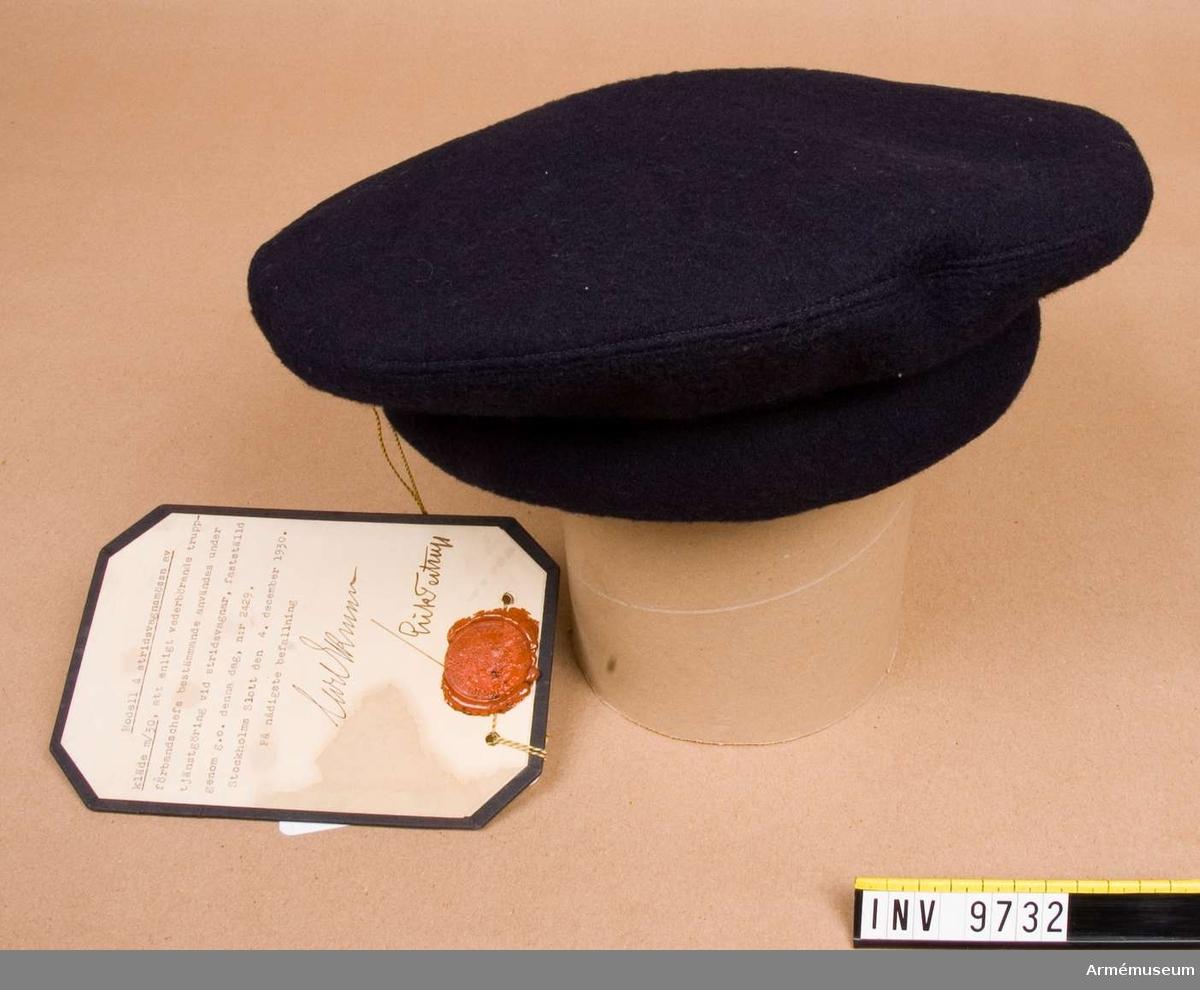 Av mörkblått kläde med stoppning i kanten över pannan och med ljustbrunt svettband.Fastställd den 4 december 1930 nr 2429.