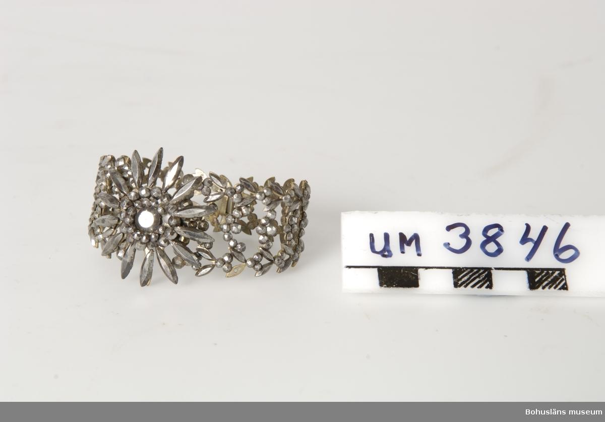 Föremålet visas i basutställningen Uddevalla genom tiderna, Bohusläns museum, Uddevalla.  Armringar i par - se UM003847 Ur handskrivna katalogen 1957-1958: Ring av metall Diam. c:a 6. Något sönder och rostad. Genombrutet metallarbete. Armband.