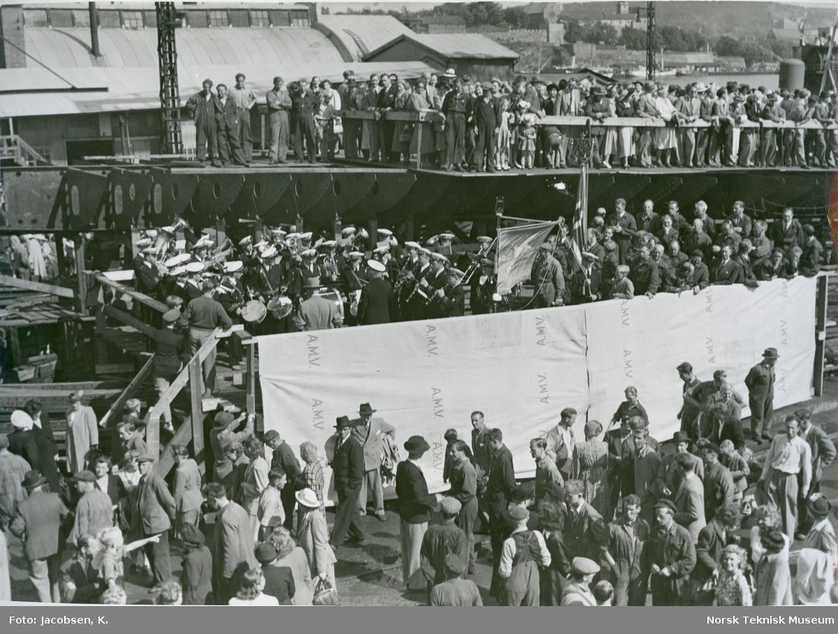 Musikkorpset og sangkoret på Akers Mek. Verksted i forbindelse med stabelavløpningen av cargolineren M/S Thermopylæ, B/N 483 29. juni 1949. Skipet ble levert i 1949 til Wilh. Wilhelmsen.