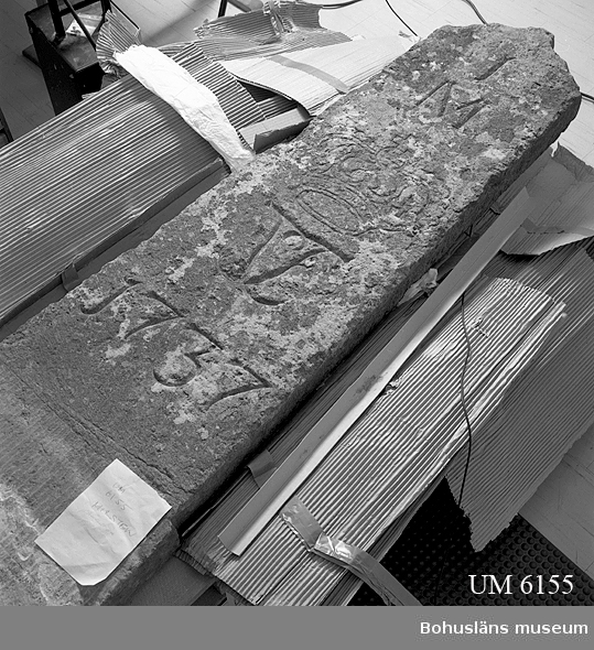 """Milsten, helmilstolpe, som markerar en gammal svensk mil,  d. v. s. 10 689 meter. Stenen kommer från rån Grinnhult, Lane-Ryr. Huggen kalksten, ortoceratitkalksten med inskriptionen:  IM [krona] 1737 Stenen kan vara bruten i Kinnekulle, Västergötland. Basen är grovhuggen i botten med en övre del huggen i refflor. Äldre skador orsakade av erosion p.g.a. väder och vind.   Redan i 1649 års skjuts- och gästgiveriförordning stadgades att häradernas vägar skulle mätas upp och förbättras. I detta arbete ingick att milstenar för varje hel mil  - 1/1 -  skulle sättas upp längs rikets landsvägar med början vid närmsta skjutsstation. Landshövdingen skulle se till att så skedde. Då Bohuslän blev svenskt 1658 skedde viss upprustning av det mycket dåliga vägnätet.  I 1734 års gästgiveriförordning stadgades att stenar skulle sättas upp också för varje halv mil -  1/2 och fjärdedels mil  - 1/4. En kvartsmil kallades """"en fjärdingväg"""".    Denna milsten ingick i den beställning som landshövdingen genomförde på 1730-talet för uppsättning längs de  bohuslänska huvudvägarna. Stenarna bär Fredrik I namnchiffer, Fredrik I svensk kung 1720-1751. De flesta stenar lär vara tillverkades vid Kinnekulle.  Systemet med milstolpar upphörde att gälla i samband med 1891 års väglag. Stenen har på sin ursprungliga plats suttit i ett stenröse, postament.  Ur handskrivna katalogen 1957-1958: Milstolpe 1737 H. c:a 160 cm. Största br. 55 cm. Måtten torde avse ovan mark hela stenen är ca: 240 x 85 x 14 cm. """"IM (krona) 1737"""". Föremålet helt. Från Grinnhult, Lane-Ryr, Bäve i Bohuslän.  Milstenen var under många år utställd på Uddevalla museums innergård, Kungsgatan.  Lappkatalog: 40  Se Bilagepärmen UM6155 ang. ritning över stenfundamentet som plockades ner på 1980-talet och då märktes med vit färg. Detta stenfundament är tillvarataget  och består av lösa fältstenar med rester av murbruk. Materialet identifierades vid genomgång av omärkt material i basmagasinet och kan på goda grunder antas vara de stenar som"""