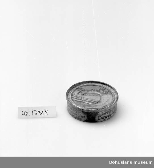 """Rund violett och vit burk, röd och violett text på locket botten och sidan: """"Brottsjö"""" lunch-sill i ostronsås."""" Tysk parallelltext på locket, engelsk på sidan samt: """"Aktiebolaget Elis Luckeys Konservfabrik, Lysekil, Sweden."""" Innehåll 42 gr. Se UM17232."""
