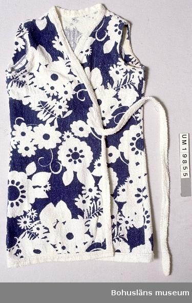 Kort badkappa utan ärmar. Av vit frotté med blått tryck (stiliserade  vita blommor mot blå bakgrund), kantad med enfärgad vit frotte. Skärp av vit frotté fastsytt i midjehöjd på båda framstyckena. Av omlottmodell där den ena skärpdelen träs igenom ett hål i den motsatta sidsömmen, lägges runt midjan bak, dras fram och knytes ihop med andra delen fram. Gulnad kring ärmhålen (svettfläckar) och nertill. Hängande trådändar här och var.